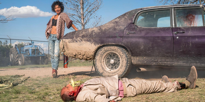 Tulipa se encostando num carro e um cara morto com um milho na boca no chão